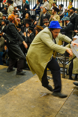 hasidic: JERUSALEM, ISRAEL - FEBRUARY 25, 2016: Jewish men attend and dance, as part of a celebration of the Jewish Holyday Purim, in the ultra-orthodox neighborhood Mea Shearim, Jerusalem, Israel
