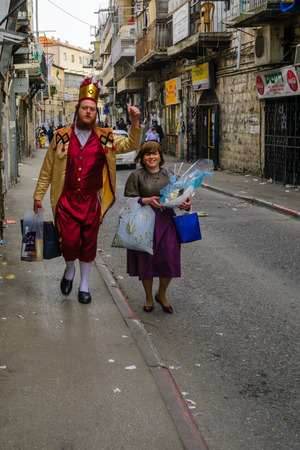 haredi: JERUSALEM, ISR - FEB 25, 2016: Street scene of people carrying mishloach manot (portions to the poor), a Jewish Holyday Purim tradition, the ultra-orthodox neighborhood Mea Shearim, Jerusalem, Israel Editorial
