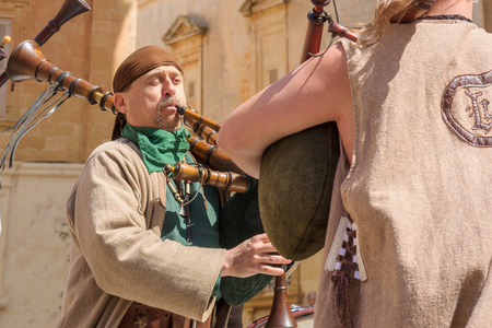 sword act: MDINA, MALTA - APRIL 14, 2012: Medieval style musicians group takes part in the Medieval Mdina festival in Mdina, Malta