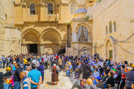 sepulcher: JERUSALEM, ISRAEL - APRIL 29, 2016: An Orthodox Good Friday scene in the yard of the church of the Holy Sepulcher, with the Greek Orthodox Patriarchate and pilgrims. The old city of Jerusalem, Israel