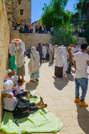 sepulcher: JERUSALEM, ISRAEL - APRIL 29, 2016: A crowd of Ethiopian Pilgrims gather in the Deir Es-Sultan, part of the church of the Holy Sepulcher, in Orthodox Good Friday. The old city of Jerusalem, Israel Editorial