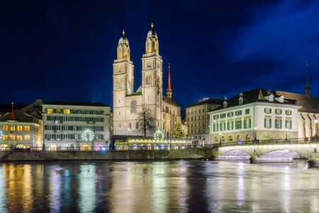 grossmunster cathedral: View of the Grossmunster (great minster) Church and the Limmat River at night, with a Christmas tree, in Zurich, Switzerland