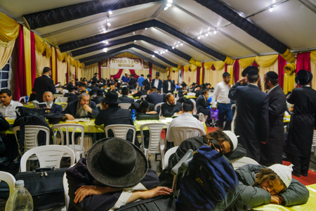 rabbi: MERON, ISRAEL - MAY 26, 2016: A crowd of orthodox Jews attend, read and nap at the annual hillulah of Rabbi Shimon Bar Yochai, in Meron, Israel, on Lag BaOmer Holiday Editorial