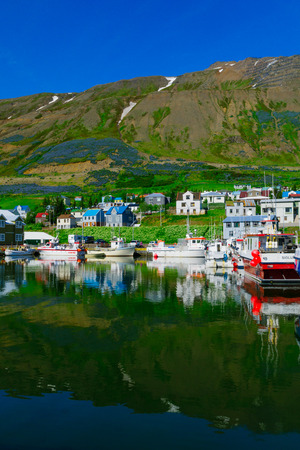 SIGLUFJORDUR, ICELAND - JUNE 18, 2016: View of the fishing port and town, with locals and tourists, in Siglufjordur, Northern Iceland