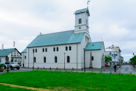 locals: REYKJAVIK, ICELAND - JUNE 11, 2016: The Cathedral (Domkirkjan), with locals and visitors, in Reykjavik, Iceland
