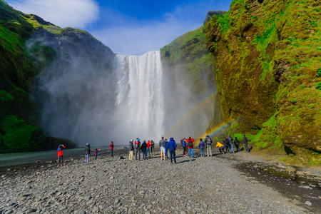 skogafoss waterfall: SKOGAR, ICELAND - JUNE 12, 2016: View of the Skogafoss waterfall, with tourists and rainbow, on the Skoga River, in south Iceland Editorial