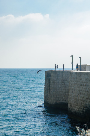 continuously: ACRE, ISRAEL - AUGUST 03, 2016: Young man jumps to the sea from the top of the ancient walls of Acre, Israel. Acre is one of the oldest continuously inhabited sites in the world Editorial
