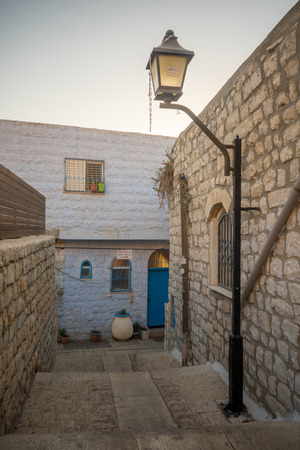jewish houses: SAFED, ISRAEL - SEPTEMBER 14, 2016: An ally in the Jewish quarter of the old city, at sunset, with various signs, in Safed (Tzfat), Israel