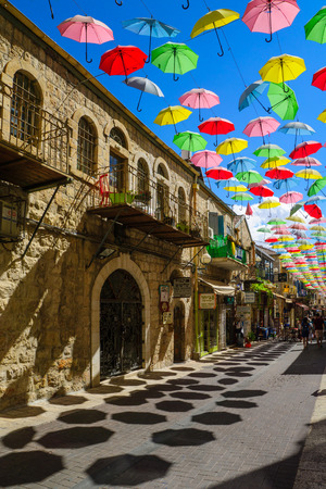 JERUSALEM, ISRAEL - SEPTEMBER 23, 2016: Scene of Yoel Moshe Solomon Street, decorated with colorful umbrellas, with locals and visitors, in the historic Nachalat Shiva district, Jerusalem, Israel Editorial