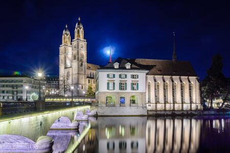 View of the Grossmunster (great minster) Church and the Limmat River at night, with a Christmas tree, in Zurich, Switzerland