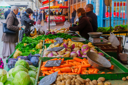 DIJON, FRANCE - OCTOBER 14, 2016: Market scene with various fruits and vegetables, sellers and shoppers, in Dijon, Burgundy, France