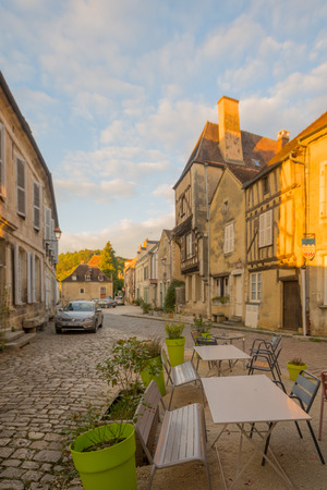 sur: NOYERS-SUR-SEREIN, FRANCE - OCTOBER 11, 2016: Sunset view of a square (place du grenier a sel), with half-timbered houses, in the medieval village Noyers-sur-Serein, Burgundy, France Editorial