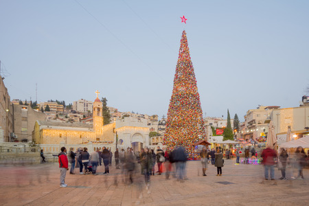 annunciation of mary: NAZARETH, ISRAEL - DECEMBER 20, 2016: Christmas scene of Mary Well square, with the Greek Orthodox Church of the Annunciation, a Christmas tree, locals and tourists, in Nazareth, Israel