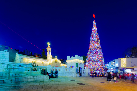 NAZARETH, ISRAEL - DECEMBER 20, 2016: Christmas scene of Mary Well square, with the Greek Orthodox Church of the Annunciation, a Christmas tree, locals and tourists, in Nazareth, Israel