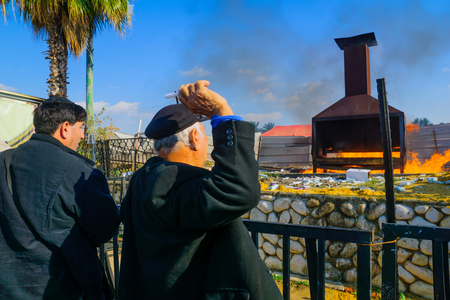 sephardic: NETIVOT, ISRAEL - JAN 30, 2017: Jewish men practice a traditional tossing of candles into a furnace, at Rabbi Israel Abuhatzeira (Baba Sali) tomb, at the annual hillula of his memory. Netivot, Israel