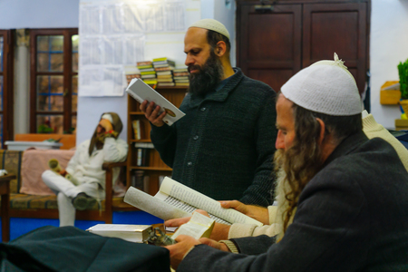 book of esther: SAFED, ISRAEL - MAR 11, 2017: Traditional Purim (Jewish Holiday) in the old Abuhav synagogue with prayers, some in costumes, attend a reading of the megillah (Scroll of Esther). Safed (Tzfat), Israel