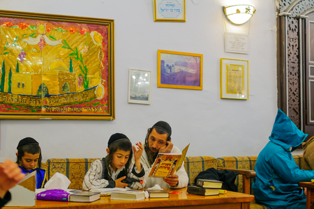 SAFED, ISRAEL - MAR 11, 2017: Traditional Purim (Jewish Holiday) in the old Abuhav synagogue with prayers, some in costumes, attend a reading of the megillah (Scroll of Esther). Safed (Tzfat), Israel