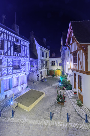 Night view of a square (place de la petite etape aux vins), with half-timbered houses, in the medieval village Noyers-sur-Serein, Burgundy, France Stock Photo