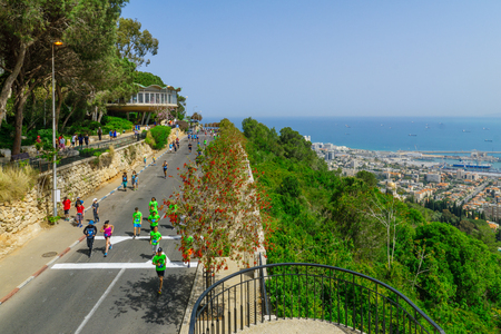 HAIFA, ISRAEL - APRIL 21, 2017: Runners participate in a popular running event for charity causes (zau larutz, get out and run) in the public streets of Haifa, Israel. With the Bahai shrine and harbor Editorial