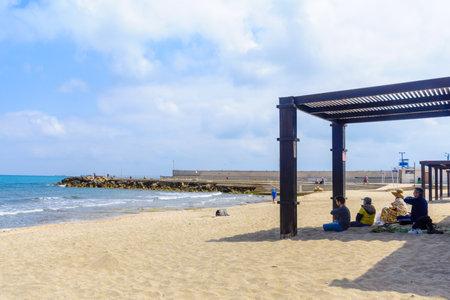 HAIFA, ISRAEL - MAY 05, 2017: Beach scene with locals, some meditating, in Bat Galim neighborhood, Haifa, Israel Editorial