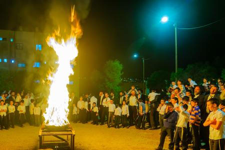 HAIFA, ISRAEL - MAY 13, 2017: A crowd of ultra-orthodox Jews gather around a fire, as part of the Lag BaOmer holiday celebration, in Haifa, Israel Editorial