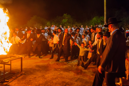 HAIFA, ISRAEL - MAY 13, 2017: A group of ultra-orthodox Jews dance around a fire, as part of the Lag BaOmer holiday celebration, in Haifa, Israel