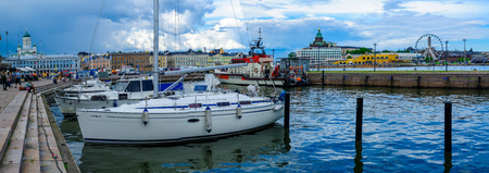 lutheran: HELSINKI, FINLAND - JUNE 16, 2017: Panoramic view of the south harbor, with the Lutheran Cathedral, the Russian Orthodox Uspenski Cathedral, the SkyWheel, locals and visitors, in Helsinki, Finland