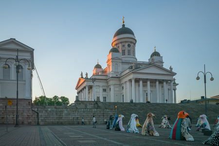 lutheran: HELSINKI, FINLAND - JUNE 15, 2017: Sunset scene in the Senate square and the Lutheran Cathedral, with a display of seal sculptures, locals and visitors, in Helsinki, Finland