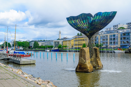 TURKU, FINLAND - JUNE 23, 2017: View of the Harmonia fountain sculpture and the Aura river, with locals and visitors, in Turku, Finland