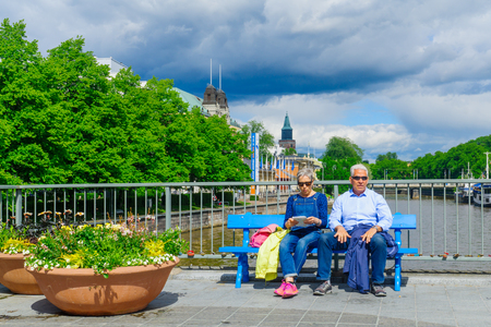 TURKU, FINLAND - JUNE 23, 2017: View of the Theatre bridge, and the Aura river, with couple resting, and other visitors, in Turku, Finland Editorial