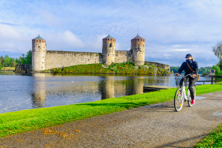 SAVONLINNA, FINLAND - JUNE 18, 2017: View of the Olavinlinna castle, with a cyclist, in Savonlinna, Finland. It is a 15th-century three-tower castle