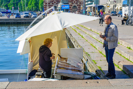suomi: HELSINKI, FINLAND - JUNE 16, 2017: Scene of the South Harbor Market Square, with a fish seller on a boat, shopper and other visitors, in Helsinki, Finland Editorial