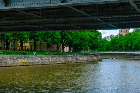 TURKU, FINLAND - JUNE 23, 2017: View of the Aura river, with the cathedral, locals and visitors, in Turku, Finland