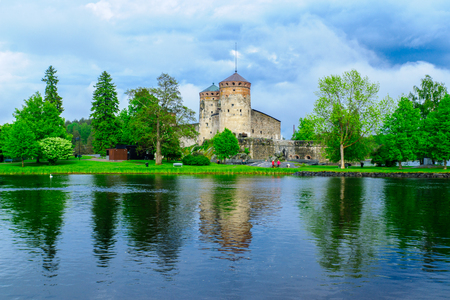 SAVONLINNA, FINLAND - JUNE 18, 2017: View of the Olavinlinna castle, with a swan and visitors, in Savonlinna, Finland. It is a 15th-century three-tower castle Editorial