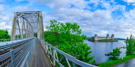 Panoramic view of a train bridge and the Olavinlinna castle in Savonlinna, Finland. It is a 15th-century three-tower castle