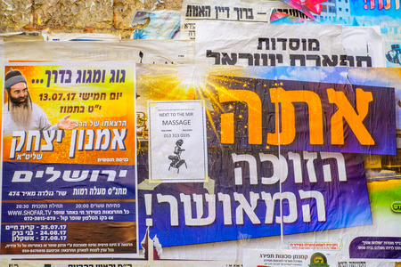 JERUSALEM, ISRAEL - JULY 12, 2017: Combination of posters about religious preaching, lottery and massages, in the ultra-orthodox neighborhood Mea Shearim, Jerusalem, Israel