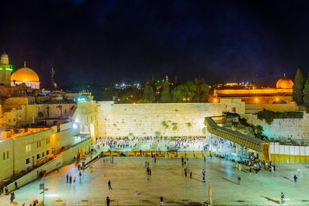 JERUSALEM, ISRAEL - SEPTEMBER 06, 2017:  Night scene of the Western Wall with Jewish prayers, and the Dome of the Rock in the background, in Jerusalem, Israel