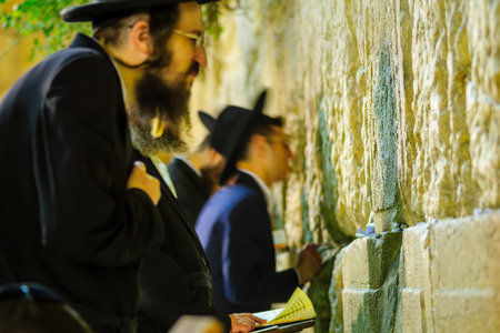 JERUSALEM, ISRAEL - SEPTEMBER 06, 2017:  Night scene of the Western Wall with various Jewish prayers, in Jerusalem, Israel. This is the holiest place in Jewish tradition