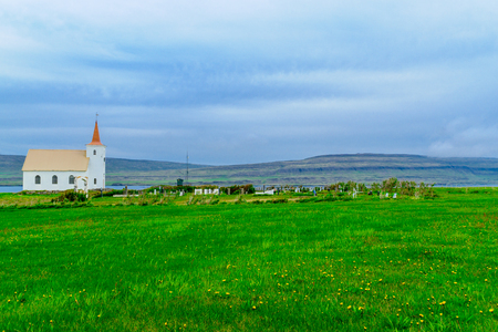 Countryside and a secluded church along the Kollafjordur fjord, in the west fjords region, Iceland