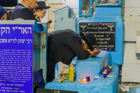 SAFED, ISRAEL - SEPTEMBER 27, 2017: Jewish men pray Selichot (penitential pray), and kneel in pray, at the tomb of The ARI (Rabbi Isaac Luria), in the old cemetery of Safed (Tzfat), Israel Editorial
