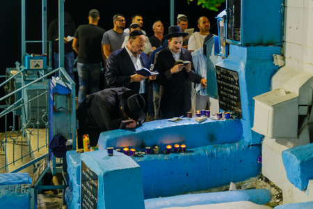 SAFED, ISRAEL - SEPTEMBER 27, 2017: Jewish men pray Selichot (penitential pray) at the tomb of The ARI (Rabbi Isaac Luria), in the old cemetery of Safed (Tzfat), Israel