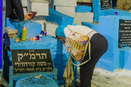 SAFED, ISRAEL - SEPTEMBER 27, 2017: Jewish woman kneel in pray, as part of the Selichot (penitential pray) at the tomb of The ARI (Rabbi Isaac Luria), in the old cemetery of Safed (Tzfat), Israel