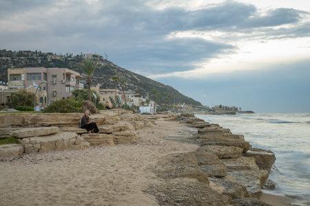 HAIFA, ISRAEL - OCTOBER 16, 2017: Sunset scene at the Bat-Galim beach, with visitors, in Haifa, Israel Editorial