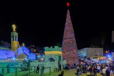 NAZARETH, ISRAEL - DECEMBER 16, 2017: Christmas scene of Mary Well square, with the Greek Orthodox Church of the Annunciation, a Christmas tree, locals and tourists, in Nazareth, Israel Editorial