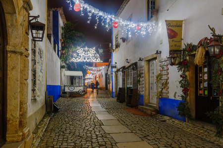 OBIDOS, PORTUGAL - DECEMBER 27, 2017: View of an alley in the old town, with local businesses, Christmas decorations, locals and visitors, in Obidos, Portugal Editorial