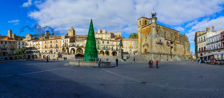 TRUJILLO, SPAIN - DECEMBER 30, 2017: Panoramic view of Plaza Mayor, with San Martin church, a Christmas tree, locals and visitors, in Trujillo, Extremadura, Spain