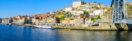 PORTO, PORTUGAL - DECEMBER 24, 2017: Panoramic view of the Dom Luis I Bridge, the Douro river and the Ribeira (riverside), with colorful buildings, locals and visitors, in Porto, Portugal Editorial