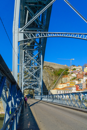 PORTO, PORTUGAL - DECEMBER 24, 2017: View of the Dom Luis I Bridge, with colorful buildings, locals and visitors, in Porto, Portugal Editorial