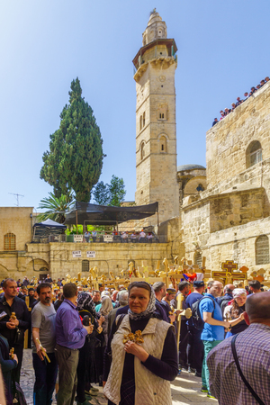 Jerusalem, Israel - April 6, 2018: Orthodox good Friday scene in the entry yard of the church of the holy sepulcher, with pilgrims carrying crosses. The old city of Jerusalem, Israel Editorial