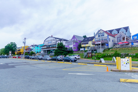 Lunenburg, Canada - September 21, 2018: View of the port and waterfront buildings, with locals and tourists, in Lunenburg, Nova Scotia, Canada